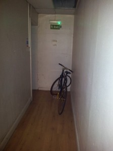 A bicycle left in a hallway obstructing the fire exit door.